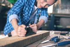 Ένας ξυλουργός εξετάζει το ξύλο σε ένα εγχώριο εργαστήριο, προγραμματισμένες σανίδες πλανίζοντας μηχανών του ξύλου Στοκ φωτογραφίες με δικαίωμα ελεύθερης χρήσης