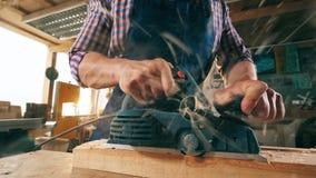 Ένας ξυλουργός περικόπτει το ξύλινο ραβδί με ένα όργανο φιλμ μικρού μήκους