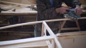 Ένας ξυλουργός γυαλίζει ένα κομμάτι του ξύλου στο ναυπηγείο φιλμ μικρού μήκους