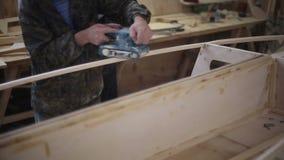 Ένας ξυλουργός γυαλίζει ένα κομμάτι του ξύλου στο ναυπηγείο απόθεμα βίντεο