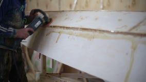 Ένας ξυλουργός γυαλίζει μια ξύλινη βάρκα στο ναυπηγείο απόθεμα βίντεο