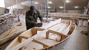 Ένας ξυλουργός γυαλίζει την ξύλινη βάρκα λεπτομερειών στο ναυπηγείο φιλμ μικρού μήκους