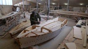Ένας ξυλουργός γυαλίζει την ξύλινη βάρκα λεπτομερειών στο ναυπηγείο απόθεμα βίντεο