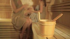 Ένας ξύλινος κάδος με το κουτάλι στο θολωμένο υπόβαθρο με τα κορίτσια που χαλαρώνουν στη σάουνα φιλμ μικρού μήκους