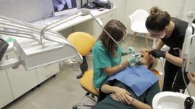 Ένας οδοντίατρος θηλυκών και ο βοηθός της που απασχολούνται στα δόντια ασθενών φιλμ μικρού μήκους