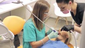 Ένας οδοντίατρος θηλυκών και ο βοηθός της που εργάζονται σε δόντια των patientαπόθεμα βίντεο