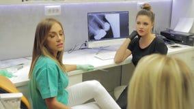 Ένας οδοντίατρος θηλυκών και ο βοηθός της που συμβουλεύονται τον ασθενή τους τι τα επόμενα βήματά τους είναι φιλμ μικρού μήκους