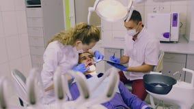 Ένας οδοντίατρος με έναν βοηθό για να πραγματοποιήσει τις διαδικασίες φιλμ μικρού μήκους