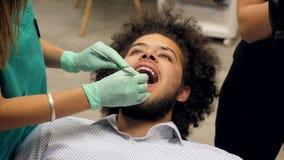 Ένας οδοντίατρος που ελέγχει έναν νεαρό τα δόντια και ο βοηθός οδοντιάτρων γράφει τι πρέπει να επισκευαστεί απόθεμα βίντεο