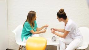 Ένας οδοντίατρος που συμβουλεύεται το βοηθό της σχετικά με τα χρώματα των οδοντικών καπλαμάδων απόθεμα βίντεο