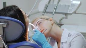 Ένας οδοντίατρος τρυπά ένα δόντι με τρυπάνι απόθεμα βίντεο