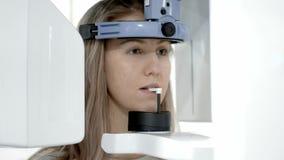 Ένας οδοντικός ανιχνευτής ακτίνας X που κάνει μια πανοραμική ακτηνογραφία του σαγονιού της νέας ξανθής γυναίκας απόθεμα βίντεο