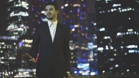 Ένας ομιλών νέος επιχειρηματίας έντυσε σε ένα μαύρο κοστούμι στη νύχτα στοκ εικόνα