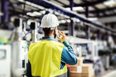 Ένας οπισθοσκόπος ενός βιομηχανικού μηχανικού ατόμων με το smartphone σε ένα εργοστάσιο, εργασία στοκ εικόνα