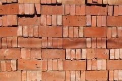 Ένας οργανωμένος σωρός των χαλαρών κόκκινων τούβλων που συσσωρεύονται ο ένας πάνω από τον άλλον Στοκ Φωτογραφίες
