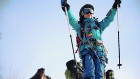 Ένας ορειβάτης βουνών νέων κοριτσιών χαίρεται για την αιχμή χαμογελά ευτυχώς και κύματα τους πόλους σκι της φιλμ μικρού μήκους