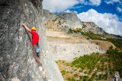 Ένας ορειβάτης βράχου σε ένα καπέλο σε έναν βράχο Στοκ Εικόνες