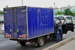 Ένας οδηγός ωθεί το αυτοκίνητο στο δρόμο Στοκ Εικόνες
