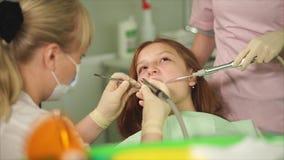 Ένας οδοντίατρος που έκανε ένα δόντι βουρτσίζοντας σε έναν έφηβο σε μια οδοντική κλινική απόθεμα βίντεο