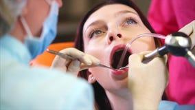Ένας οδοντικός γιατρός κλινικών ξεπλένει τα υπομονετικά δόντια ` s με το νερό και έναν καθρέφτη φιλμ μικρού μήκους