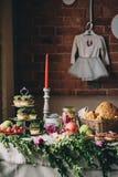 Ένας πίνακας για ένα κόμμα εξυπηρέτησε με τα κεριά, τα κέικ, το ψωμί και τα φρούτα στο υπόβαθρο ενός τουβλότοιχος Στοκ Φωτογραφίες