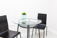 Ένας πίνακας γυαλιού και μαύρες καρέκλες στο Σκανδιναβικό ύφος στο εσωτερικό ενός φωτεινού σύγχρονου διαμερίσματος Περιοχή κουζιν στοκ φωτογραφίες με δικαίωμα ελεύθερης χρήσης
