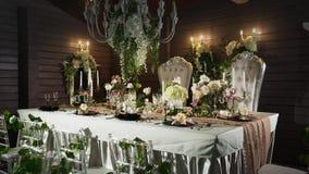 Ένας πίνακας που τίθεται με τα μαύρα βέλη με τα τρόφιμα, γυαλιά κρασιού, βάζα λουλουδιών, κηροπήγια με τα κεριά πίσω από ποιες στ απόθεμα βίντεο