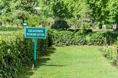 Ένας πίνακας σημαδιών σε ένα πάρκο που ενθαρρύνει τη χρήση των σκουπιδοτενεκών και κάνει το αριθ. στοκ φωτογραφίες με δικαίωμα ελεύθερης χρήσης