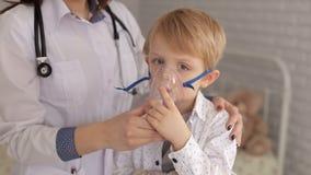 Ένας παιδίατρος γυναικών βάζει σε μια inhaler μάσκα σε ένα νέο αγόρι στο νοσοκομείο απόθεμα βίντεο
