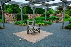 Ένας παλαιός κήπος, με μια εκλεκτής ποιότητας ξύλινη πολυθρόνα στο κέντρο μιας μικρής ανοιχτής περιοχής  βεραμάν εγκαταστάσεις κα στοκ εικόνα