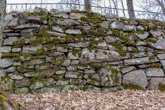 Ένας παλαιός προκαλούμενος από τον άνθρωπο τοίχος πετρών με το βρύο σε το στοκ εικόνα
