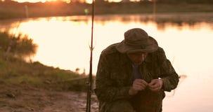 Ένας παλαιός ψαράς προσκολλάται σε ένα σκουλήκι, moldy σκουλήκι σε έναν γάντζο ράβδων αλιείας φιλμ μικρού μήκους