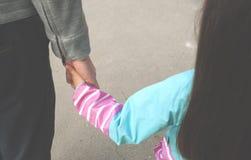 Ένας πατέρας κρατά ένα χέρι μιας κόρης στοκ εικόνες