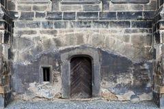 Ένας παλαιός γοτθικός τοίχος καθεδρικών ναών με μια μικρή ξύλινη πόρτα Στοκ εικόνα με δικαίωμα ελεύθερης χρήσης