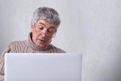 Ένας παλαιός παππούς στα γυαλιά που κάνει μια τηλεοπτική κλήση από το lap-top του που επικοινωνεί με τα παιδιά του Ένας μόνος συν Στοκ εικόνες με δικαίωμα ελεύθερης χρήσης