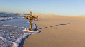 Ένας παλαιός σταυρός στον αμμόλοφο άμμου δίπλα στον ωκεανό με μια ήρεμη ανατολή Στοκ Εικόνες