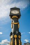 Ένας παλαιός χρυσός πύργος ρολογιών μπροστά από μια εκκλησία Στοκ Εικόνα