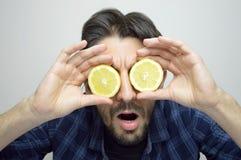 Ένας περίεργος νεαρός άνδρας που καλύπτει τα μάτια του με τα λεμόνια που ανακαλύπτουν ένα νέο πράγμα/ένα νέο προϊόν στοκ φωτογραφίες