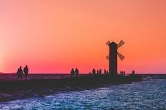 Ένας περίπατος ομάδων ανθρώπων κατά μήκος της αποβάθρας κοντά στο φάρο στη θάλασσα στο ηλιοβασίλεμα στοκ φωτογραφίες με δικαίωμα ελεύθερης χρήσης