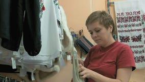 Ένας πελάτης που προσπαθεί να βρεί την τέλεια μπλούζα στο κατάστημα απόθεμα βίντεο