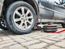 Ένας πνευματικός γρύλος βρίσκεται σε ένα πάτωμα κεραμιδιών δίπλα σε ένα σκονισμένο αυτοκίνητο σε ένα κατάστημα επισκευής αυτοκινή στοκ εικόνες με δικαίωμα ελεύθερης χρήσης