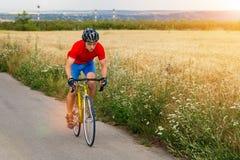 Ένας ποδηλάτης οδηγά σε ένα οδικό ποδήλατο κατά μήκος του τομέα Έντονο φως ήλιων Στοκ Εικόνα