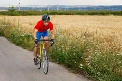 Ένας ποδηλάτης οδηγά σε ένα οδικό ποδήλατο κατά μήκος του τομέα Στοκ Φωτογραφία