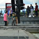 Ένας ποδηλάτης πηδά πέρα από έναν σωλήνα σε ένα ποδήλατο BMX Πολλοί άνθρωποι με Στοκ Φωτογραφία