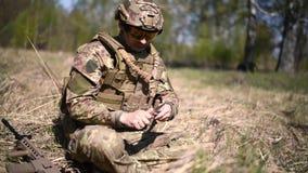 Ένας πολεμιστής ή ένας στρατιωτικός στρατιώτης που ντύνεται στην κάλυψη διακόπτει έναν κλάδο και τον χτυπά μακριά με ένα μαχαίρι φιλμ μικρού μήκους
