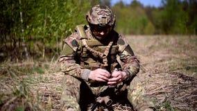 Ένας πολεμιστής ή ένας στρατιωτικός στρατιώτης που ντύνεται στην κάλυψη βγάζει τα γάντια και γυρίζει μια χειροβομβίδα στα χέρια τ απόθεμα βίντεο
