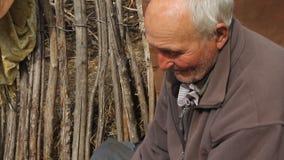 Ένας πολύ άρρωστος ηληκιωμένος κάθεται σε ένα σκαμνί κρατώντας μια αίγα στα χέρια, το παιχνίδι και τη σίτισή του απόθεμα βίντεο