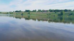 Ένας ποταμός με τις χλοώδη ακτές και τα μέρη των πράσινων δέντρων φιλμ μικρού μήκους