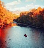 ένας ποταμός που ρέει το φθινόπωρο με ένα kayaker που κωπηλατεί στο νερό Στοκ Εικόνα