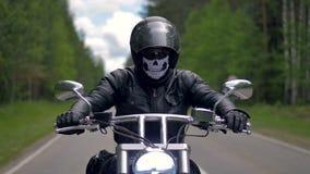 Ένας ποδηλάτης ατόμων που οδηγά μια μοτοσικλέτα που φορά τα μαύρα ενδύματα και το κράνος απόθεμα βίντεο